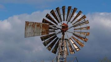 Closeup of a rusty old wind pump with sails spinning in a gentle breeze with a cloudy blue sky video