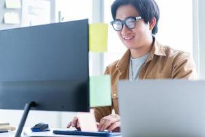 Hombre de negocios asiático que trabaja con la computadora en la oficina foto