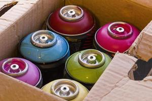 Box full of colored spray cans photo