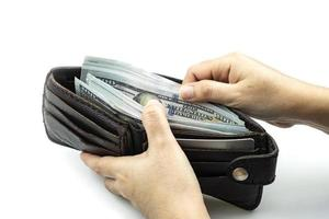 Hand holding wallet on bundles of 100 US dollars banknotes on white background photo