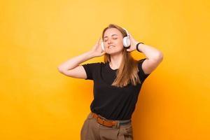 Photo of cheerful woman listening music at white wireless headphones over yellow background