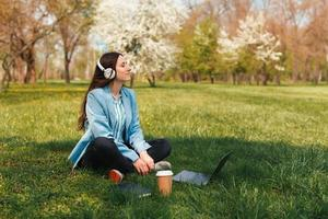 Foto de joven mujer independiente sentada en el césped de la ciudad en el parque y escuchando música frente a la computadora portátil y una taza de café