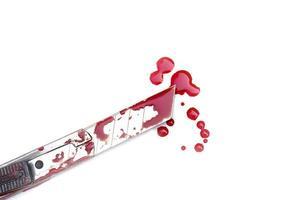 Cuchillo de corte ensangrentado sobre fondo blanco, concepto de halloween de violencia social foto