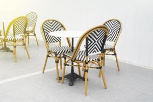 un lugar para terrazas y cafés de verano al aire libre, para tomar café en la calle de la ciudad. mesas y sillas de madera vacías. foto