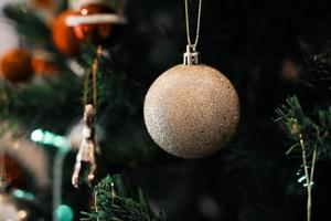 Golden Christmas balls on a green Christmas tree, close up. Christmas and New Year Decoration. photo