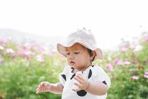 Young little cute asian girl playing in cosmos flower field in spring or summer season. photo