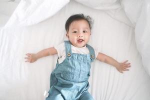 sonriente niña asiática acostada en una cama. foto