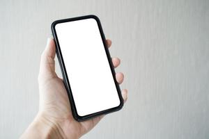 mano de hombre sosteniendo smartphone con pantalla en blanco sobre fondo gris, primer plano de la mano. espacio para texto. foto