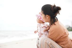 madre e hija disfrutando en la playa. hermosas vacaciones familiares vacaciones de verano. foto