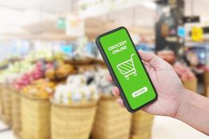 mano de hombre sosteniendo el teléfono inteligente contra el desenfoque bokeh de fondo de la tienda. comestibles en línea. foto