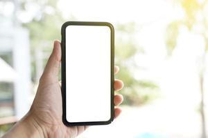 maqueta de teléfono móvil de pantalla en blanco. Mano de hombre sosteniendo y usando un teléfono móvil con pantalla blanca en blanco contra el bokeh del fondo de la naturaleza. foto