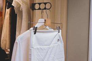 White shirt and skirt hanging in the closet. photo