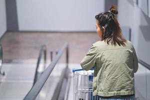 mujer con carrito de compras en escaleras mecánicas en mega tienda. foto