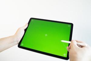 mano dibuja un lápiz en una tableta con un chromakey en la pantalla. foto