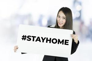 empresaria con hoja de papel blanco con hashtag quedarse en casa. Llame para quedarse en casa durante una epidemia de coronavirus para protegerse contra el virus. foto
