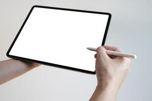 mano usando la pantalla en blanco táctil de la pluma de la tableta digital. manos sosteniendo y escribiendo en tableta digital. foto