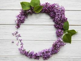 Marco de ramas y flores de color lila en forma de círculo. foto