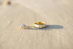par de anillo de bodas en la playa foto