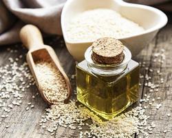 aceite de sésamo y semillas en una mesa rústica. foto