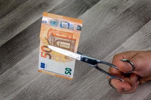 Hombre cortando billetes de 50 euros con unas tijeras foto