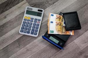 Billetes en euros en la parte superior de una escala con calculadora cercana foto
