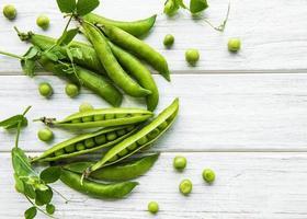 guisantes verdes sobre un fondo de madera blanca. Fondo de comida sana. foto