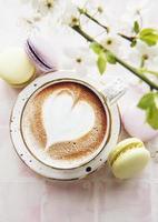 café con un patrón en forma de corazón y postres dulces de macarrones foto