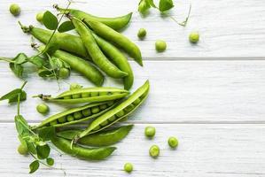 guisantes verdes sobre un fondo de madera blanca. fondo de comida sana foto