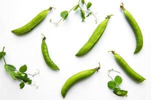 guisantes verdes sobre un fondo blanco. fondo de comida sana foto
