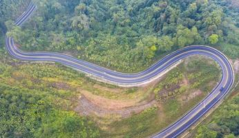 Aerial top view of a road in the forest photo