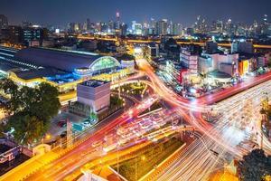 Fondo nocturno de la ciudad moderna, los senderos de luz en el edificio moderno en Bangkok, Tailandia foto