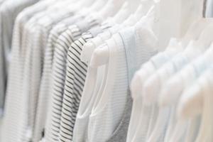 Colección de ropa de bebé colgada en la sala de exposiciones. foto