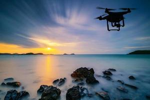 Silhouette of drone flying over sea with clouds passing photo