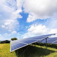 Solar panels power station on green field under blue sky photo