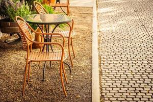 Silla vacía y mesa alrededor de cafetería y restaurante al aire libre foto
