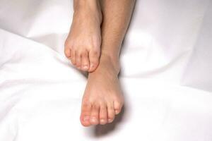 Mujer flexión del pie en las sábanas de color blanco foto
