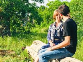 pareja joven sentada en la rama de un árbol foto
