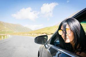 Mujer caucásica de pelo oscuro asomando desde la ventana del coche foto