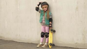 A cheerful little girl stands with a yellow skate in her hands and smiles video