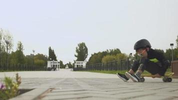 A preschooler boy with a protective helmet rides a skateboard in Park Summer video