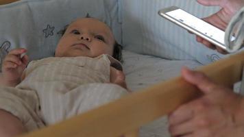 l'enfant joue avec le mobile dans le berceau maman se tient près du lit et utilise le téléphone video