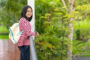Chica estudiante asiática de pie en el parque de la escuela en un día soleado de verano foto