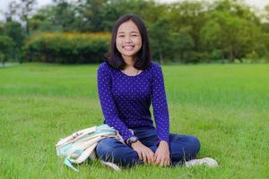 Chica estudiante asiática sentada y sonriendo en el parque en un día soleado de verano foto