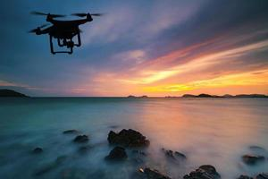 Silhouette of drone flying over sea at sunset photo