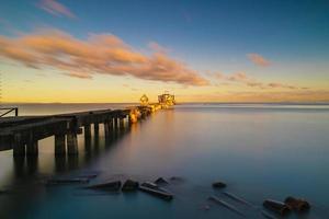 The old bridge into the sea on the beach at sunrise photo