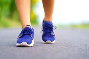Piernas de mujer caminando en el parque, corredora corriendo en la carretera exterior foto