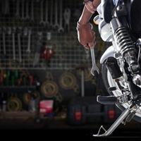 Vista recortada del mecánico con una llave en una motocicleta foto