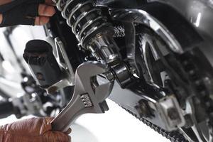 Vista recortada del mecánico con una llave en una motocicleta sobre fondo blanco. foto