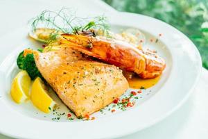 Mixed grilled seafood steak with salmon prawn and other meat photo