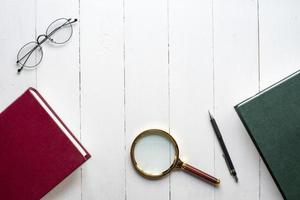 Education concept, book ,pen, eyeglasses, magnifying glass on white wood background photo